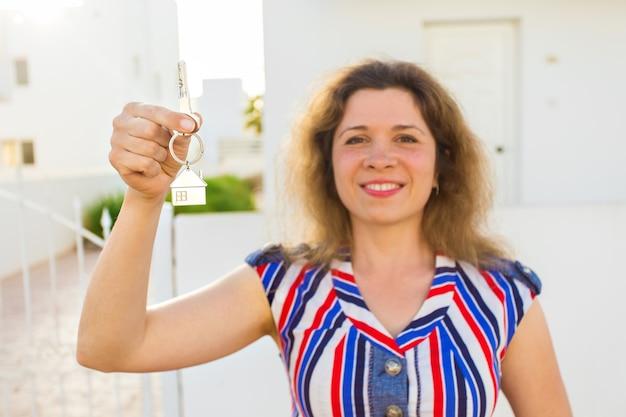 Концепция новоселья, недвижимости, собственности и переезда - новый владелец дома с ключом.