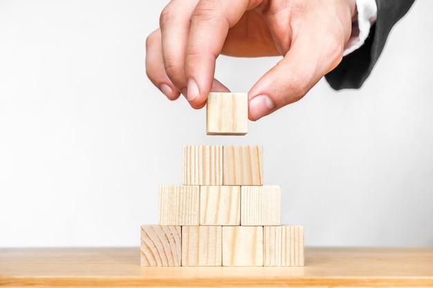 人的資源管理と採用ビジネスの概念ビジネスの成功の概念に手でピラミッドの上に木製の立方体ブロックを置きます。