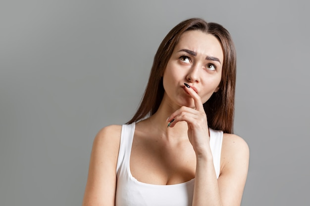 Понятие идеи и поиска информации. портрет задумчивой молодой женщины кавказа, которая смотрит с хмурым взглядом. серый фон. скопируйте пространство.