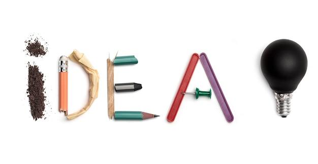 カラフルなしわくちゃの紙でアイデアのコンセプト。オフィスの文房具から生まれたアイデアという言葉。アート、クリエイティブ、文字の概念。概念的なイメージ。白い机の上に隔離された上面図。作業工具のコンセプト