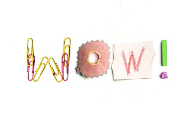 カラフルなしわくちゃの紙でアイデアのコンセプト。オフィスの文房具から作られた「すごい」という言葉。アート、クリエイティブ、文字の概念。概念的なイメージ。白い机の上に隔離された上面図。作業工具のコンセプト
