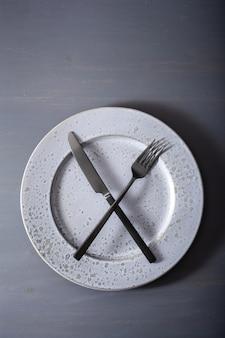 断続的な断食とケトン食、減量の概念。フォークとナイフが皿の上を渡った