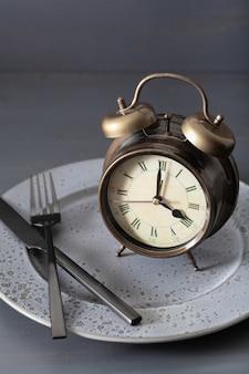 断続的な断食、ケトン食、減量の概念。フォークとナイフが交差し、プレートに目覚まし時計