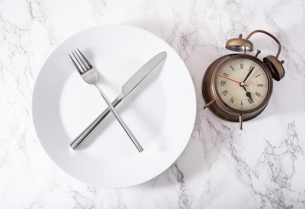断続的な断食、ケトン食、減量の概念。フォークとナイフが皿と目覚まし時計で交差