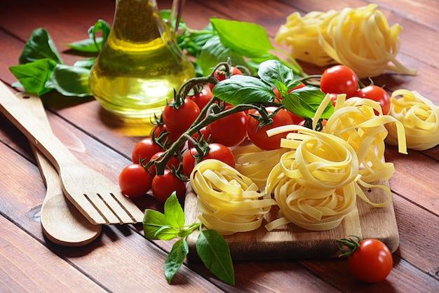 生パスタ、トマト、バジル、油でイタリア料理のコンセプト