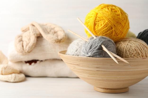 Концепция вязания на белом деревянном столе.