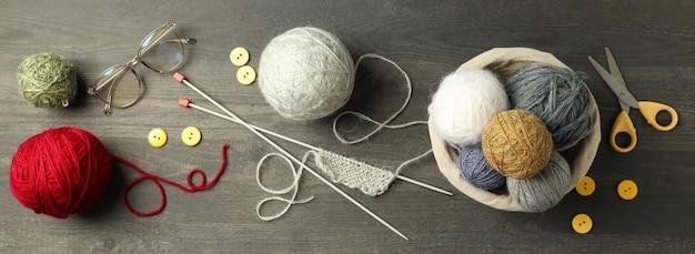 Концепция вязания с шариками пряжи на сером деревянном столе