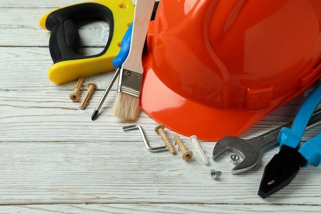 Концепция дня труда с различными строительными инструментами на белом деревянном