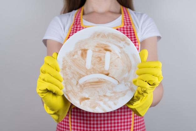 Понятие лени от скуки. обрезанное фото крупным планом руки, держащей показывая несчастный смайлик в руках на тарелке, изолированном сером фоне