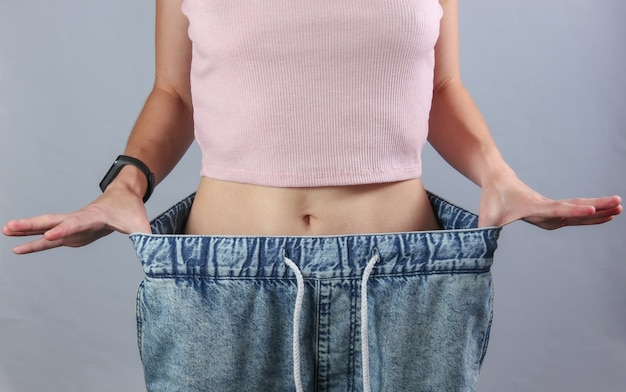 体重を減らすという概念。灰色のスタジオの背景に非常に大きなジーンズの女性。