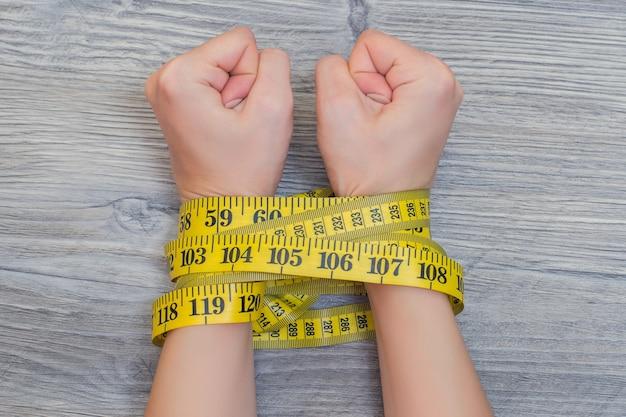 体重を減らすという概念。黄色の巻尺で結ばれた女性の手。