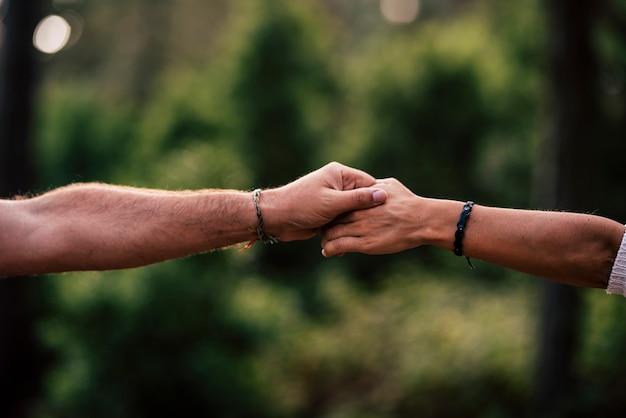愛の概念とお互いの人々や関係を助けます-触れたり、保持したり、助けたりする手のクローズアップ-緑のボケの焦点がぼけた背景