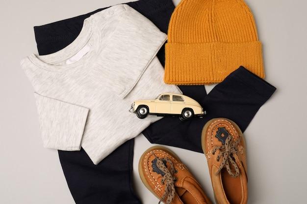 Концепция мужской детской одежды на светло-сером фоне.