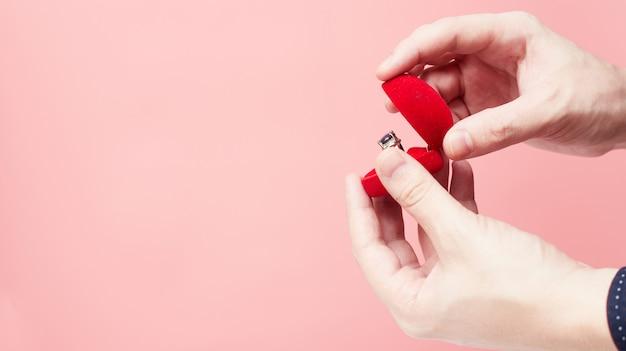 Концепция предложения руки и сердца, день святого валентина, на розовом фоне