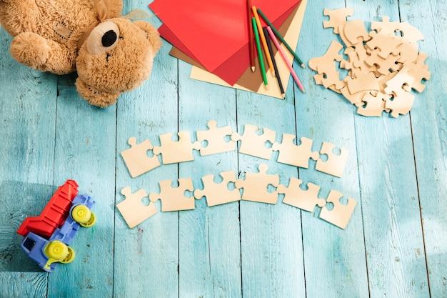Концепция макета и кусочков головоломки на фоне деревянного стола