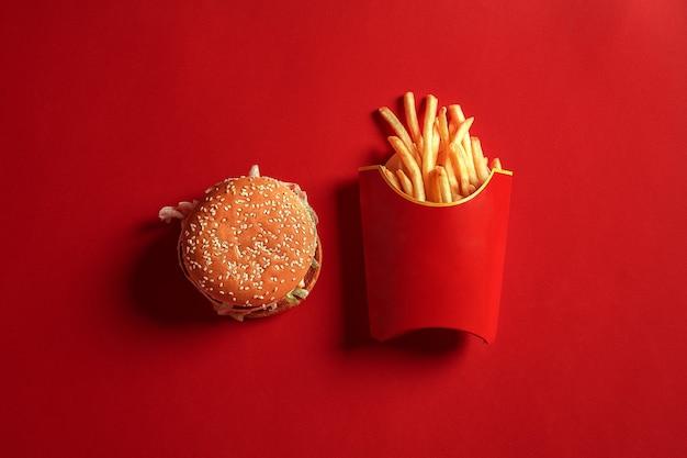 Концепция макета гамбургера и картофеля фри на красном фоне копирует пространство для текста и логотипа