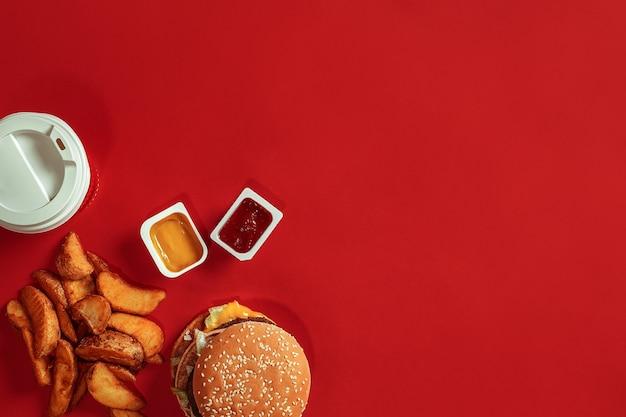 Концепция макета соуса и напитка из гамбургера с картофелем на красном фоне, копией пространства для текста и логотипа
