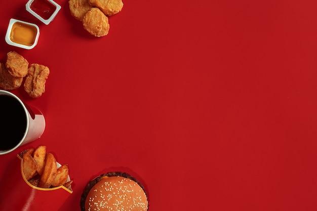 Концепция макета гамбургера с картофелем, соусом из куриных наггетсов и напитком на красном фоне, копией пространства для ...