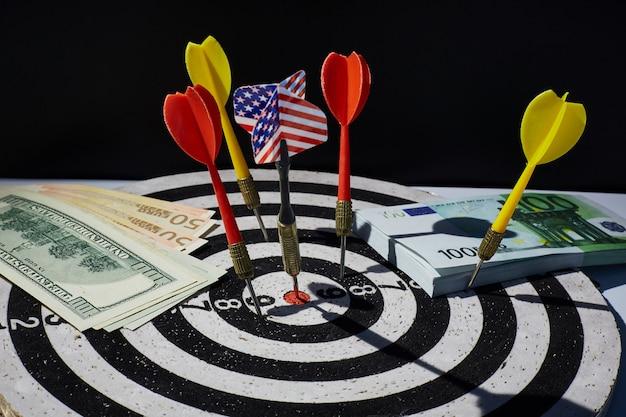 通貨インフレや金利の概念。アメリカの旗が付いたダーツ、ユーロとアメリカの紙幣が100ドル前後のターゲット。