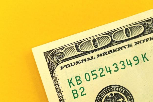 オフィステーブルのクローズアップ、黄色の背景写真に100ドル札とお金の預金の概念