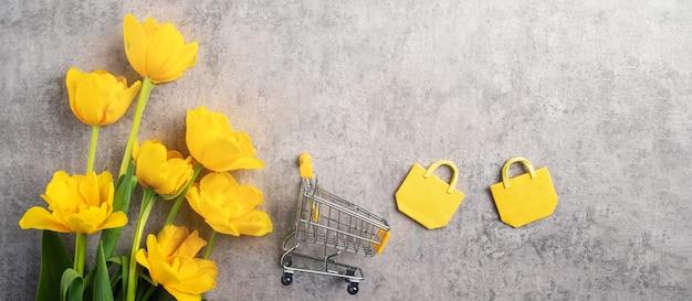 회색에 노란색 튤립 꽃 꽃다발과 어머니의 날 휴일 선물 쇼핑 인사말 디자인의 개념