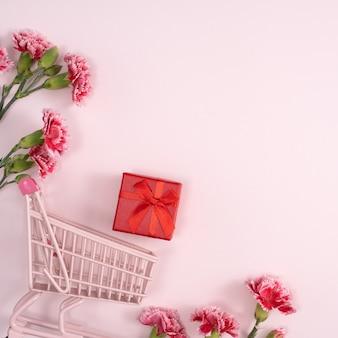 분홍색 배경에 카네이션 꽃다발과 선물 어머니의 날 휴일 인사말 디자인의 개념