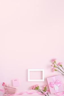 분홍색 표면에 카네이션 꽃다발과 선물 어머니의 날 휴일 인사말 디자인의 개념