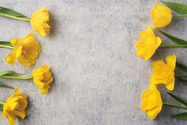 회색 배경에 노란색 튤립 꽃 부케와 어머니의 날 휴일 인사말 디자인의 개념