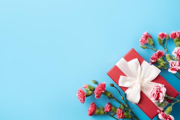 밝은 파란색 테이블 배경에 카네이션 꽃다발과 어머니의 날 휴일 인사말 선물 디자인의 개념