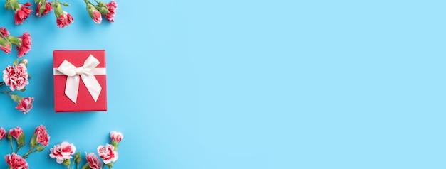 밝은 파란색 테이블 배경에 카네이션 꽃다발과 어머니의 날 휴일 인사말 선물 디자인의 개념 프리미엄 사진