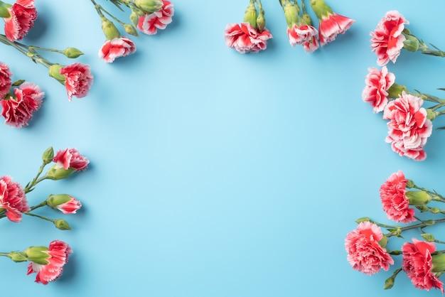 밝은 파란색 테이블 표면에 카네이션 꽃다발과 어머니의 날 휴일 인사말 선물 디자인의 개념