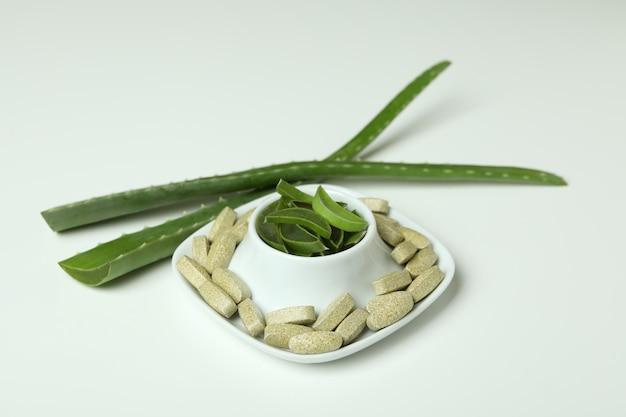 白い背景の上のアロエと天然ハーブの丸薬の概念