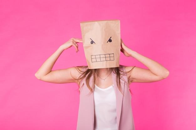 부정적인 감정의 개념 - 얼굴에 종이 봉지를 얹은 화난 여자.