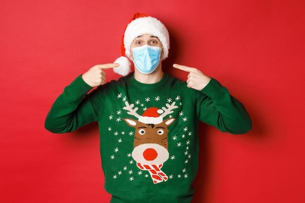 새해, 코로나바이러스, 사회적 거리의 개념. 산타 모자와 크리스마스 스웨터를 입은 행복한 남자, 파티에서 의료용 마스크를 착용할 것을 권장하고 빨간색 배경 위에 서 있습니다