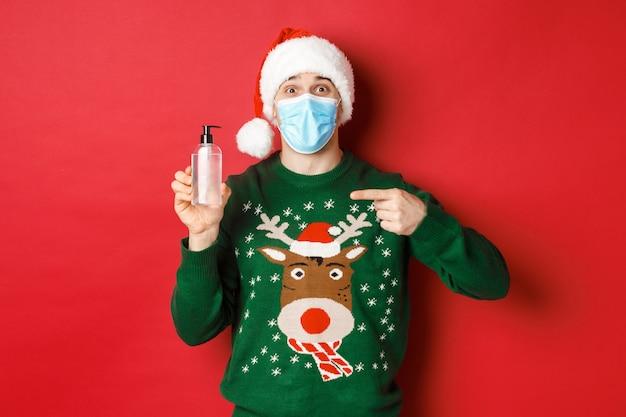 새해, 코로나바이러스, 사회적 거리의 개념. 산타 모자, 크리스마스 스웨터, 의료용 마스크를 쓴 쾌활한 남자의 초상화, 손 소독제를 손가락으로 가리키며 빨간 배경 위에 서 있습니다.