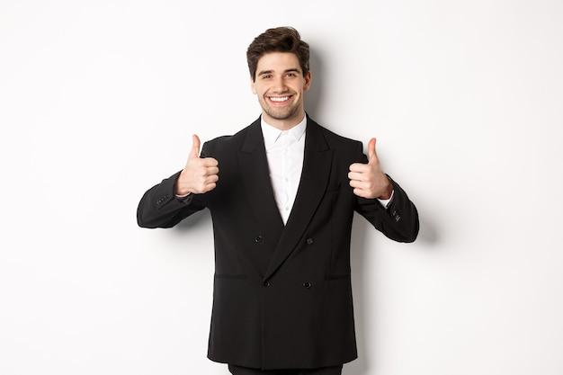 新年会、お祝い、ライフスタイルのコンセプト。フォーマルなスーツを着た魅力的な幸せなビジネスマンの画像。白い背景の上に立って、親指を立てて笑顔で、好きで、承認します。
