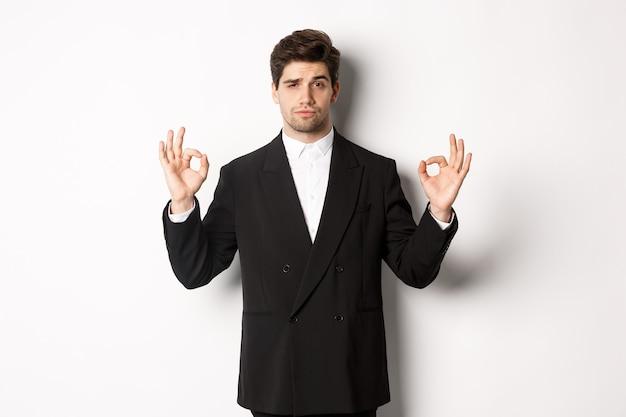 新年会、お祝い、ライフスタイルのコンセプト。白い背景の上に立って、大丈夫なサインを示して何かを承認する、黒いスーツを着た自信のあるハンサムな男の肖像画