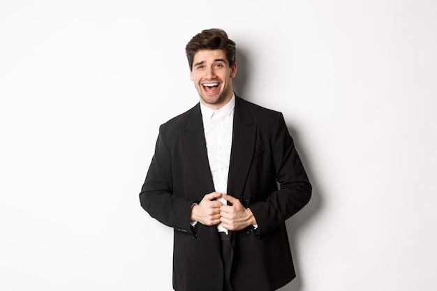 新年会、お祝い、ライフスタイルのコンセプト。スーツを着たハンサムで自信に満ちた男の肖像画、満足して笑って、成功を感じ、白い背景の上に立っています。