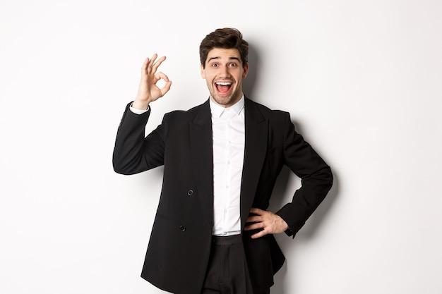 新年会、お祝い、ライフスタイルのコンセプト。黒のスーツを着た喜んでいるハンサムな男の肖像画は、白い背景の上に立って、承認の大丈夫なサインを示して、何か良いものを賞賛します。