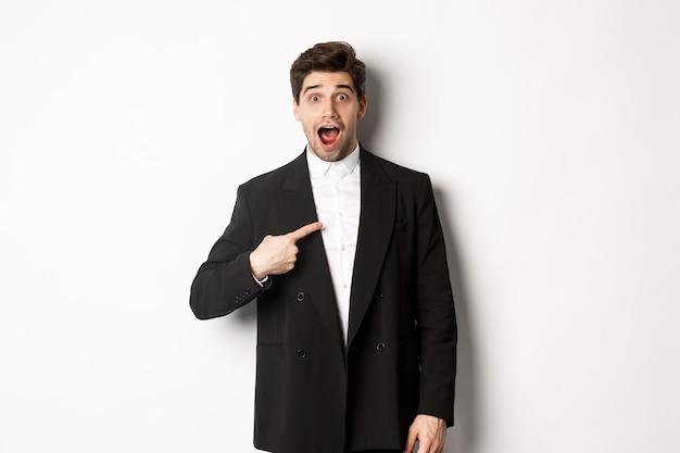 신년 파티, 축하 및 라이프 스타일의 개념입니다. 검은 양복을 입은 놀란 잘생긴 남자의 초상화, 자신을 가리키며 놀란 표정을 하고, 선택을 받고, 흰색 배경 위에 서 있습니다.