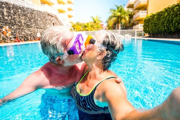 無制限の年齢の概念と夏休みの休暇中に楽しんでプールで一緒にキスする白人の幸せな高齢者のカップルとの関係