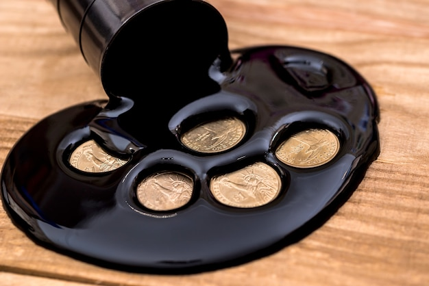 Концепция нефтяного бизнеса на деревянном столе, масло и монета