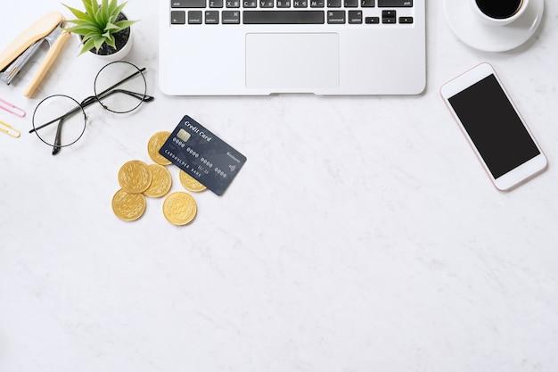 Концепция онлайн-платежей с помощью кредитной карты со смартфоном, портативным компьютером на офисном столе на чистом ярком мраморном столе, вид сверху, плоская планировка