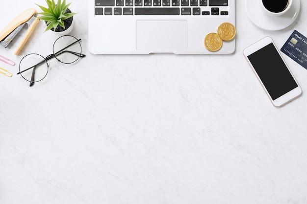 きれいな明るい大理石のテーブルの背景にオフィスの机の上のスマートフォン、ラップトップコンピューターとクレジットカードでオンライン支払いの概念