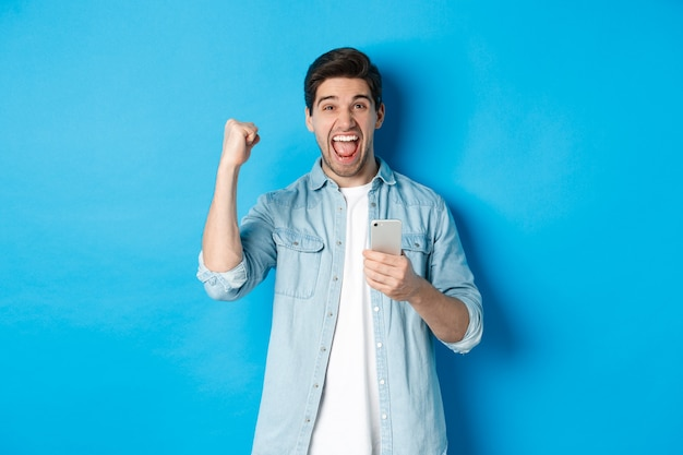 オンラインショッピング、アプリケーション、テクノロジーの概念。興奮した男は、青い背景の上に立って、スマートフォンで勝った後、イエスと叫び、ガッツポーズのジェスチャーをします