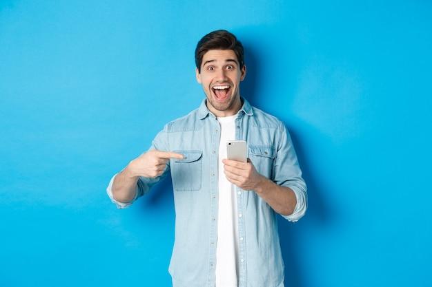 オンラインショッピング、アプリケーション、テクノロジーの概念。青い背景に驚いて立って、電話で指を指している幸せな笑顔の男