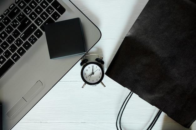 オンラインショッピング、インターネット決済、eコマース、モックアップ、黒いバッグ、白い背景のノートブックと時計のコンセプト、販売コンセプト、ブラックフライデー、フラットレイ、コピースペース、フリーテキストスペース