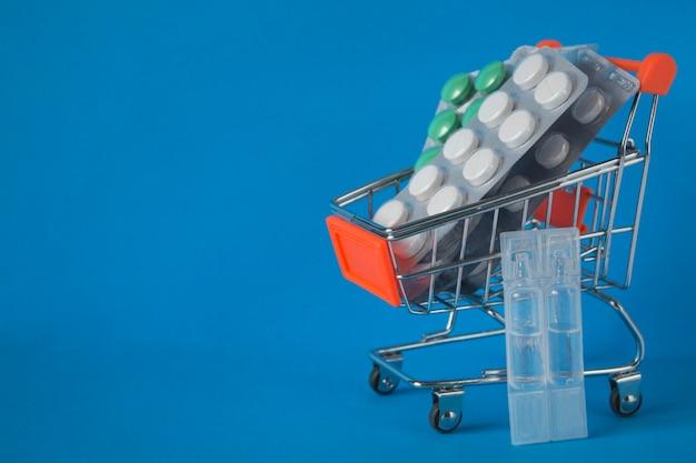 온라인 쇼핑, 주문 및 의약품 배달의 개념. 파란색 배경에 쇼핑 카트에 약 물집 팩