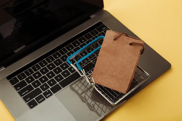 オンラインショッピングの概念。黄色で隔離のラップトップのキーボード上の紙の買い物袋とカート