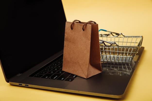 Концепция покупок в интернете. бумажная хозяйственная сумка и тележка на клавиатуре ноутбука.